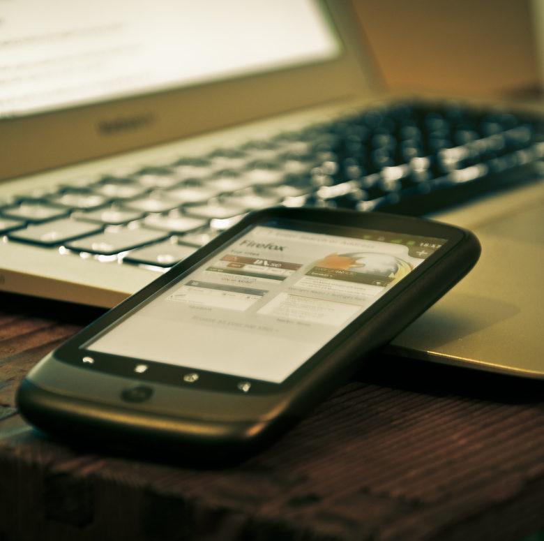 Foto de um smartphone encostado em um notebook