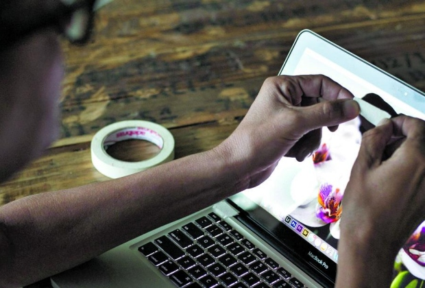 Foto de um usuário tampando a câmera de seu MacBook com uma fita