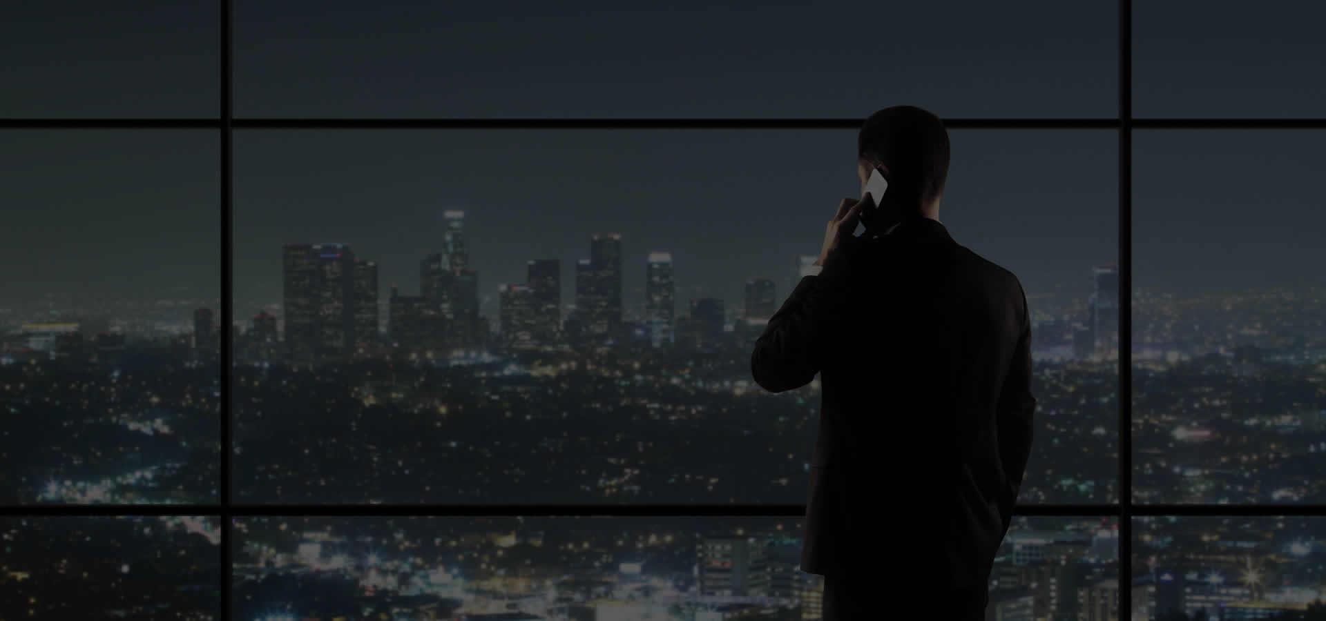 Fundo de tela executivo olhando para a cidade a noite do alto de um prédio